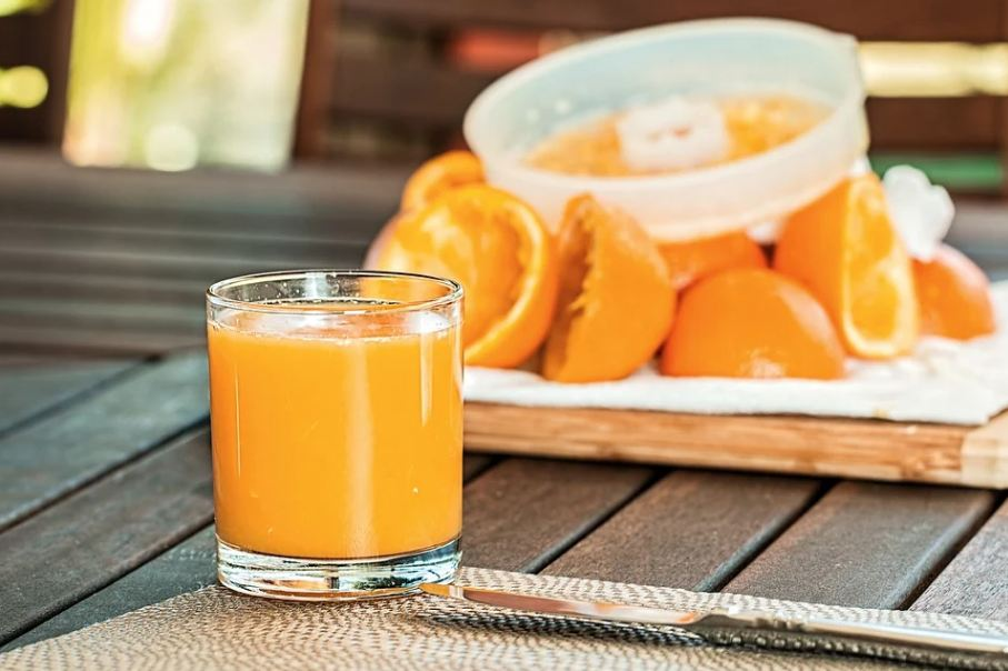 a glass of orange juice with used orange peels in the background
